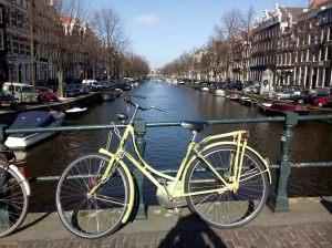 Ein Fahrrad an einer Gracht in Amsterdam: Die Niederländer sind Fahrrad-Weltmeister. Dort sind die meisten Menschen ohne Helm unterwegs.